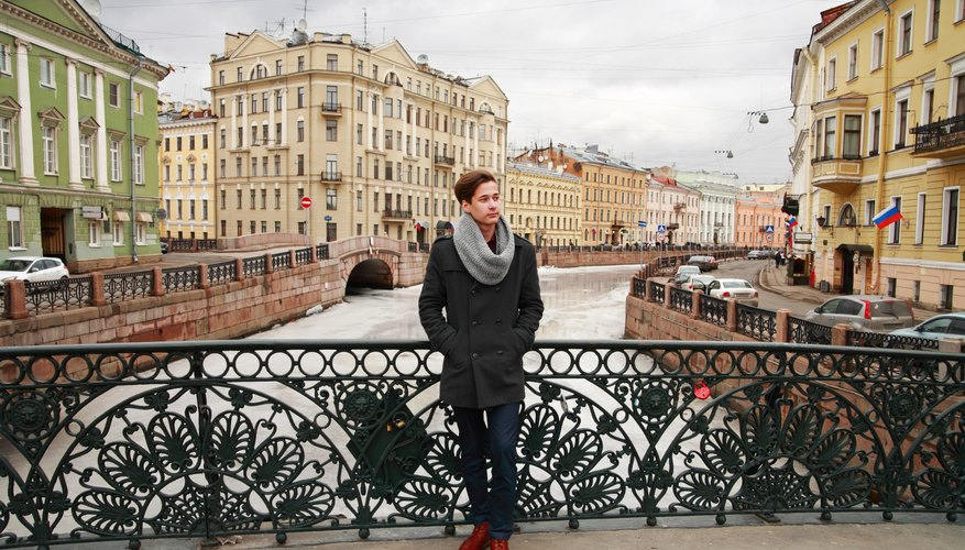 A young Russian man standing on a bridge.