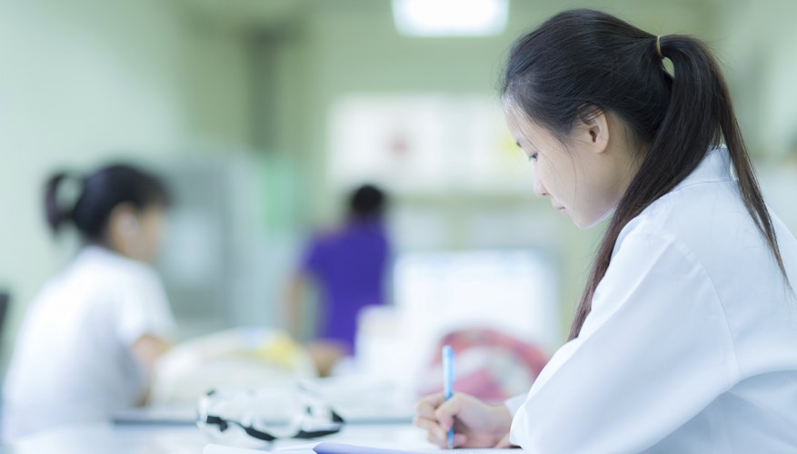 A researcher writing at a table in a laboratory.