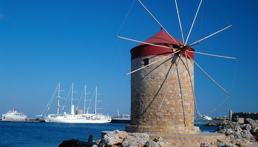Windmill on coast along water's edge.
