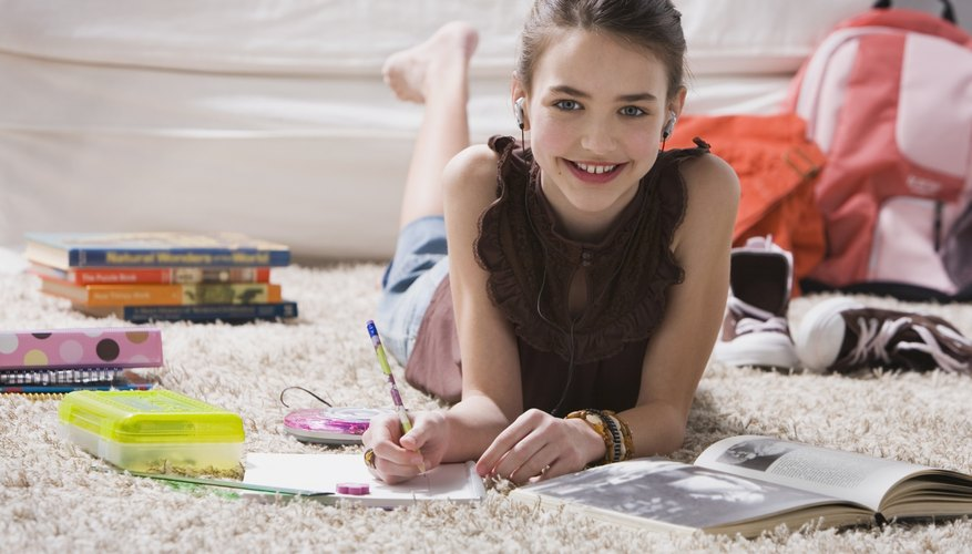 A girl does homework on the living room floor.