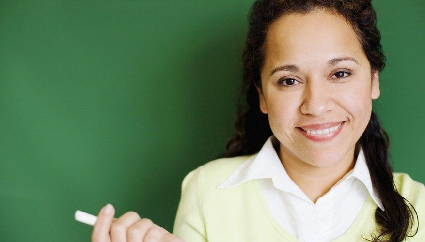 Smiling teacher holding piece of chalk