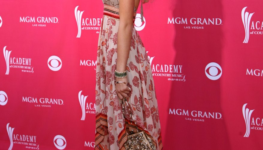 Taylor Swift accessorizes her red carpet dress with a pair of classic cowboy boots.