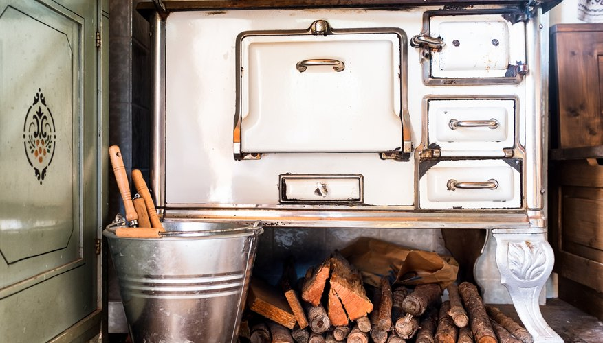 An antique cooking stove and wood pile in an old farmhouse.