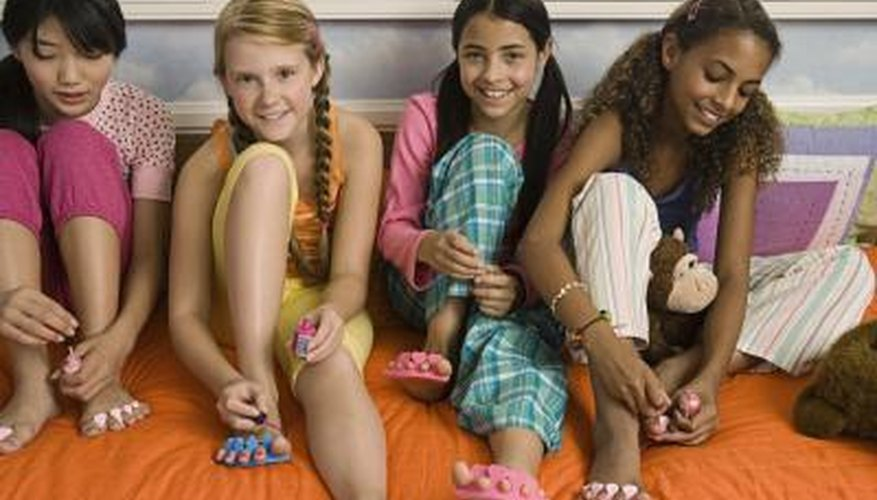 Young girls give pedicures at spa parties.