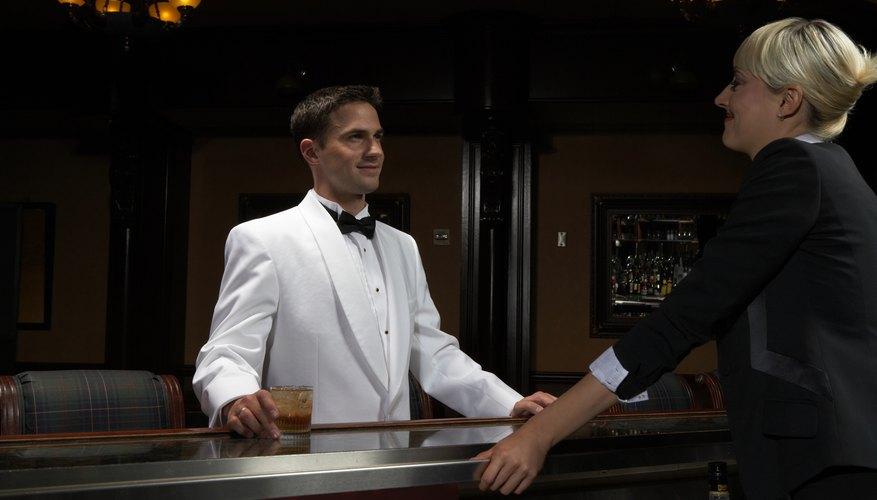 A bartender wears a white tuxedo jacket.
