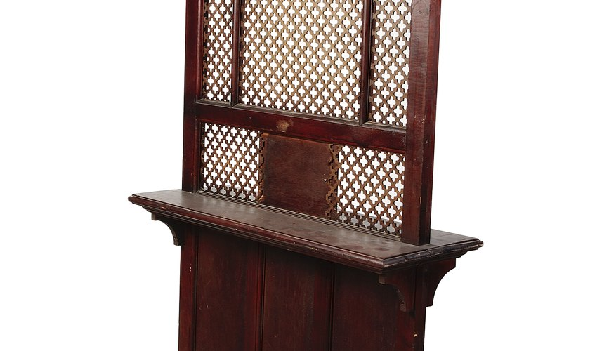 Catholic confession to a priest takes place through a wooden screen, as pictured, or face to face.