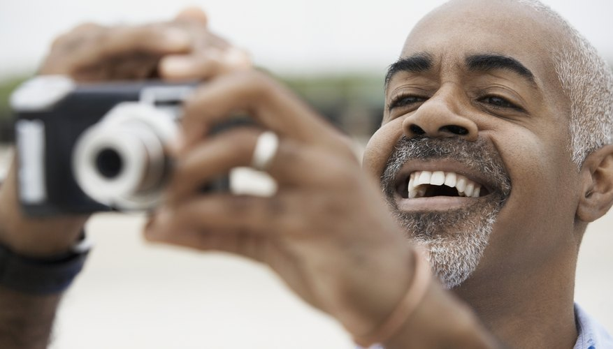 Man using a digital point and shoot camera.