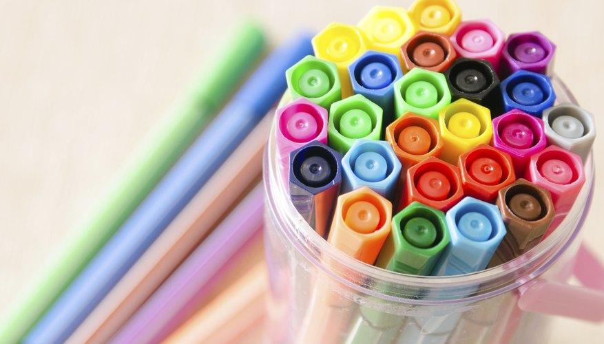 Markers stored in a plastic cup.