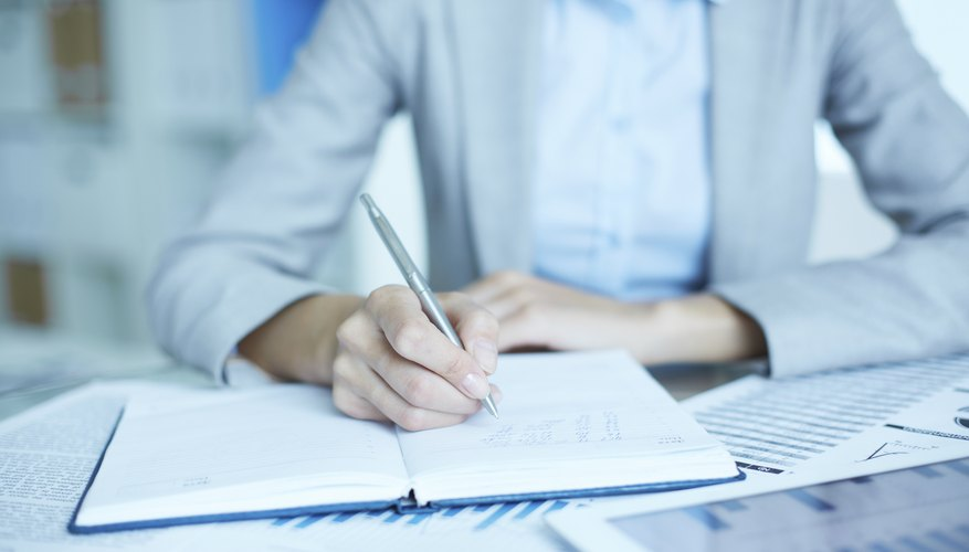 Woman writing in notebook on work desk