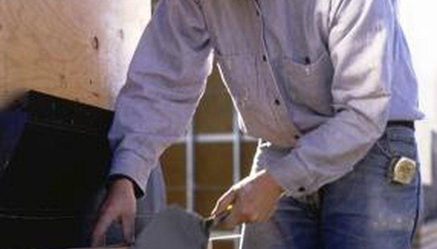 Mason workers use a masonry hammer to lay bricks.
