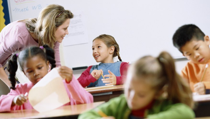Teacher helping young children with schoolwork in classroom