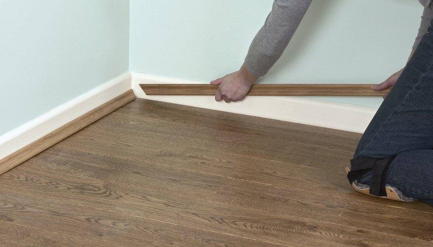 Finish laminate flooring around the edge of the room with trim.
