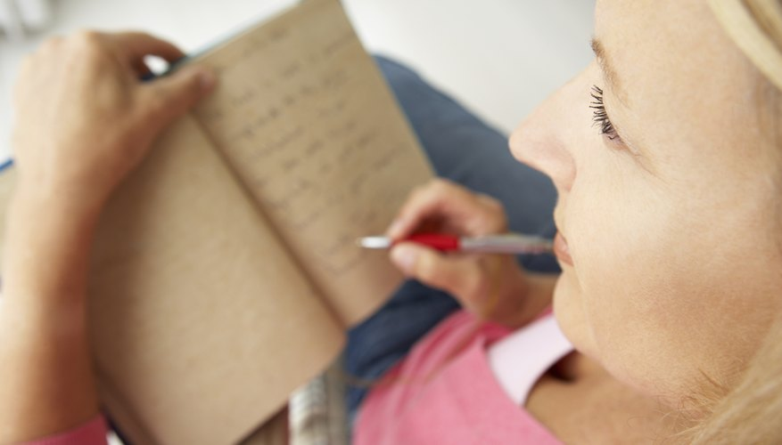 A woman ponders while writing in a notebook.
