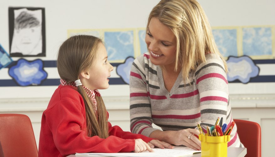Speech therapist working with young student at desk.