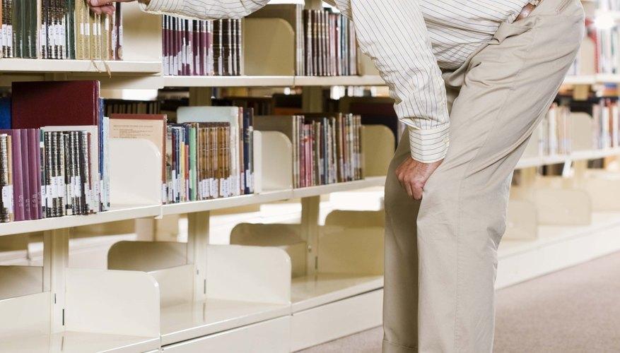 Hombre buscando un libro en un estante.