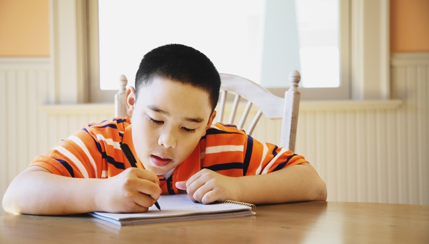 Young boy writing in notebook at kitchen table.