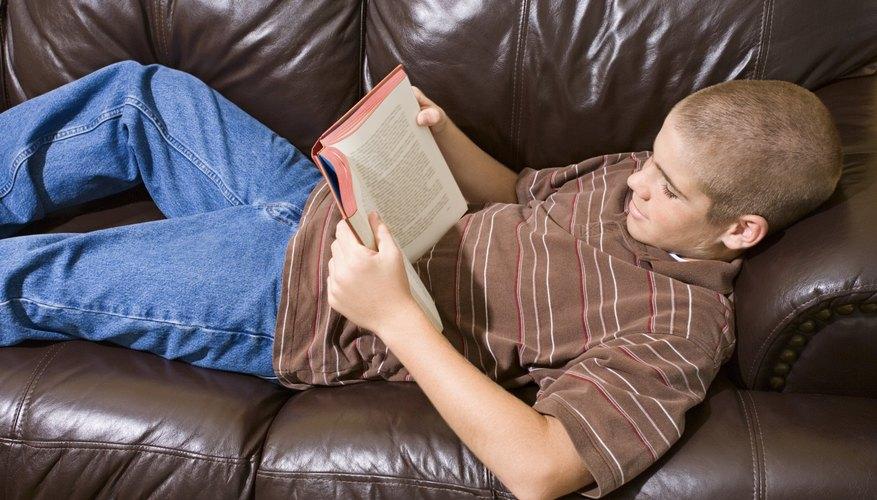 Teenage boy reading a boy on a couch.