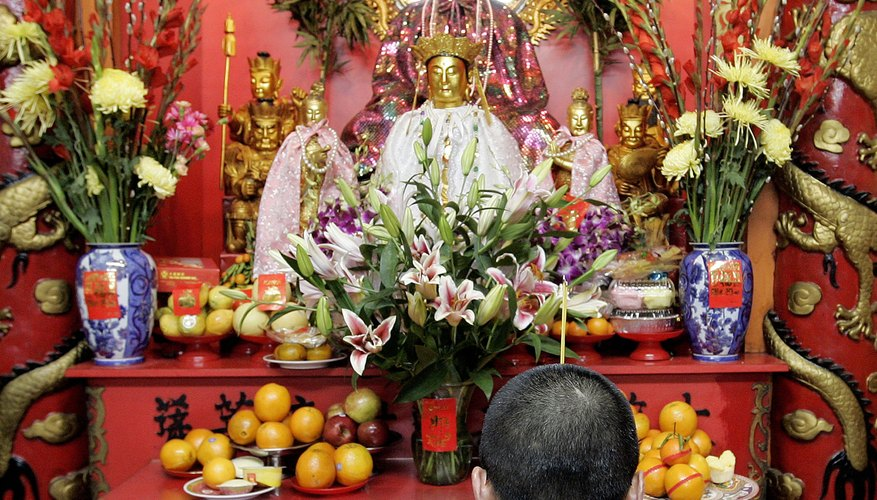 A man prays in front of the statues on a typical temple shrine.