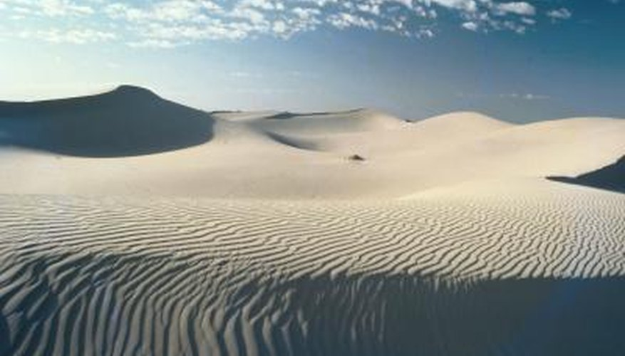 Sand dunes are created when sand is deposited by the wind.