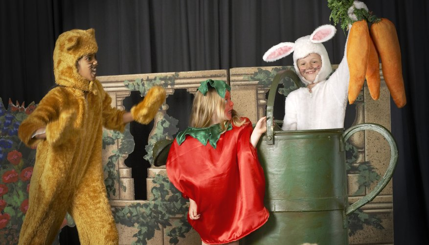 Three young children are dressed in costume and performing on stage.