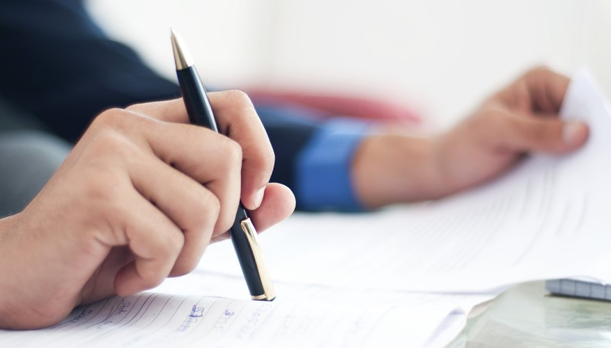Close-up of man filling out paperwork
