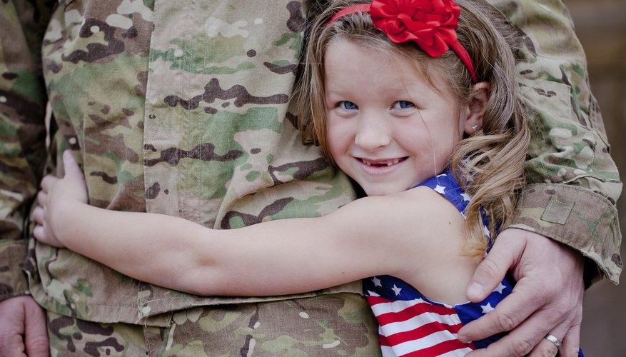Little girl hugging soldier