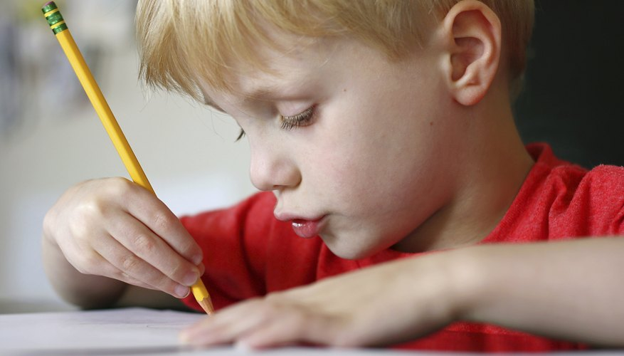 A young boy is writing an essay.