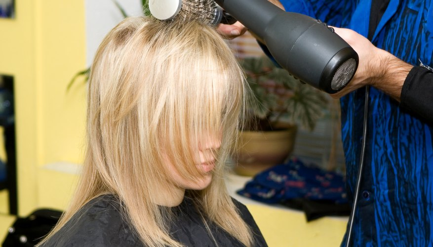 A woman in a salon is getting her hair blow dried.