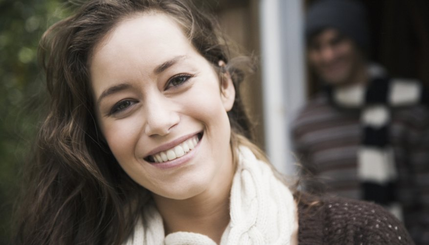 A close-up of a happy woman with a man smiling in the doorway behind her.