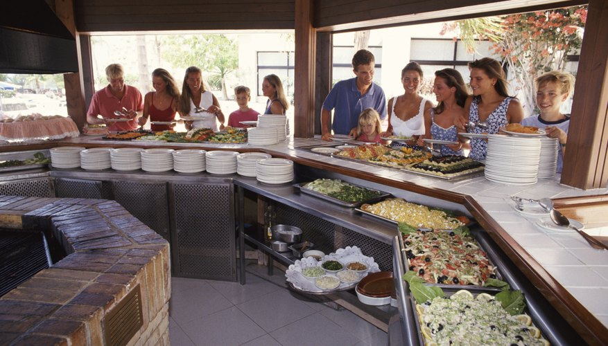 A group of people are standing at a buffet.