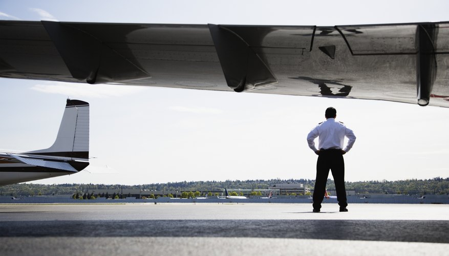 An airline pilot standing on the tarmac under the wing of a plane.