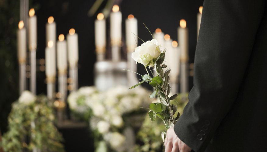 Person holding a rose in front of casket at funeral.
