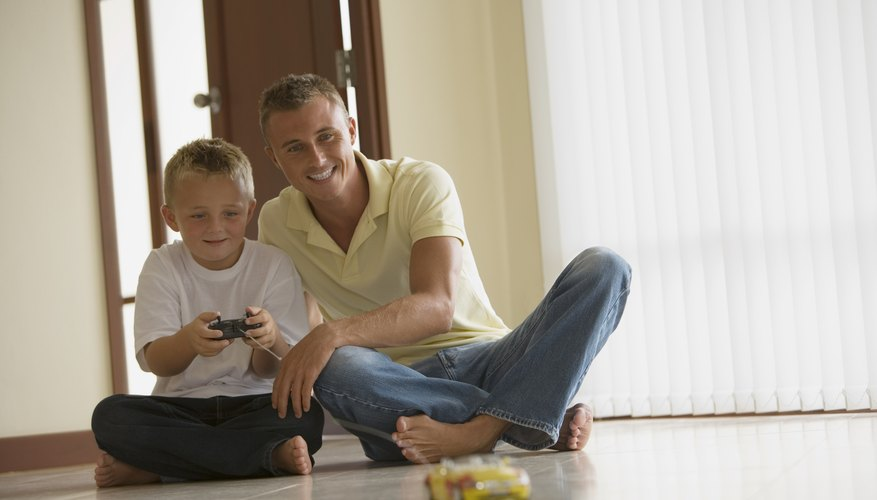 Child and father playing with remote control car.