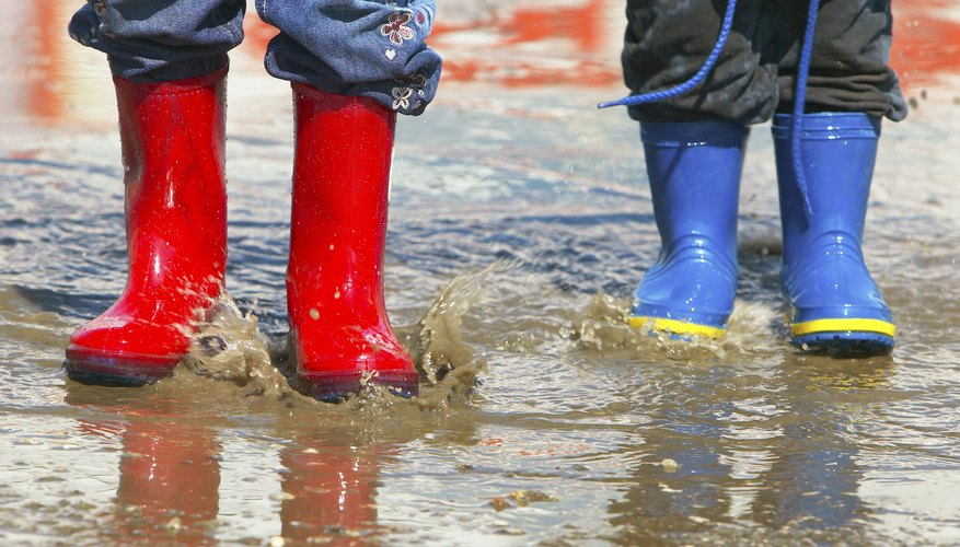 Young kids in rain boots in a puddle.