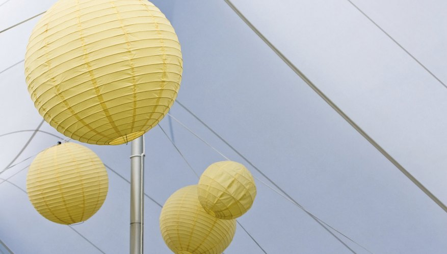 Paper lanterns hang from the apex of an outdoor tent.