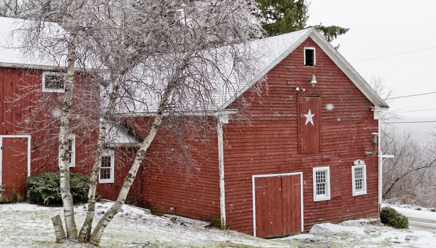 A white star on the front of a red barn on a winter morning.