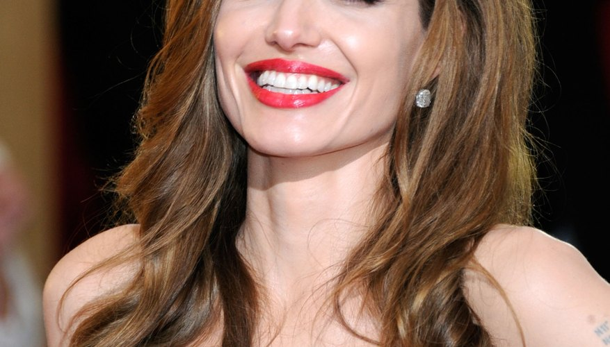 With a black gown, diamond solitaire earrings and bold red lips, Jolie wears all her fashion staples.