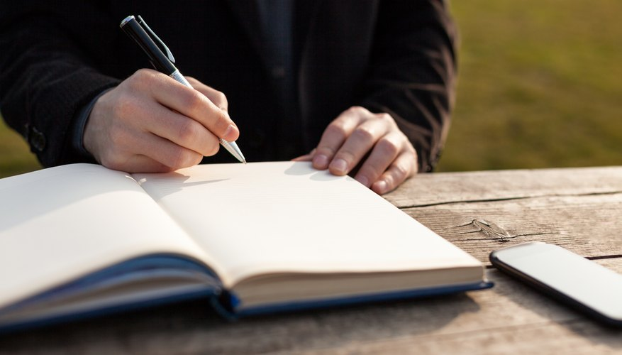 A man writing in a journal at an outdoor table.
