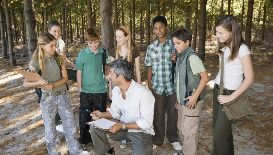 Teacher and students in the woods.