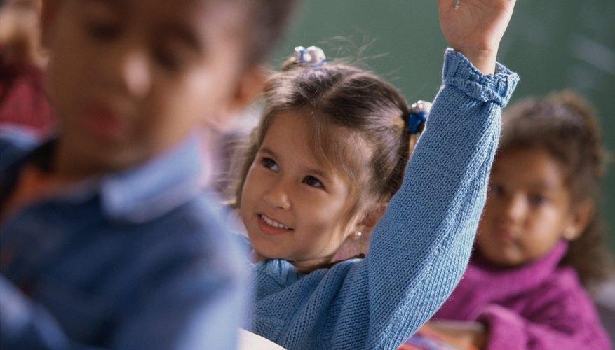 Little girl raising hands in class