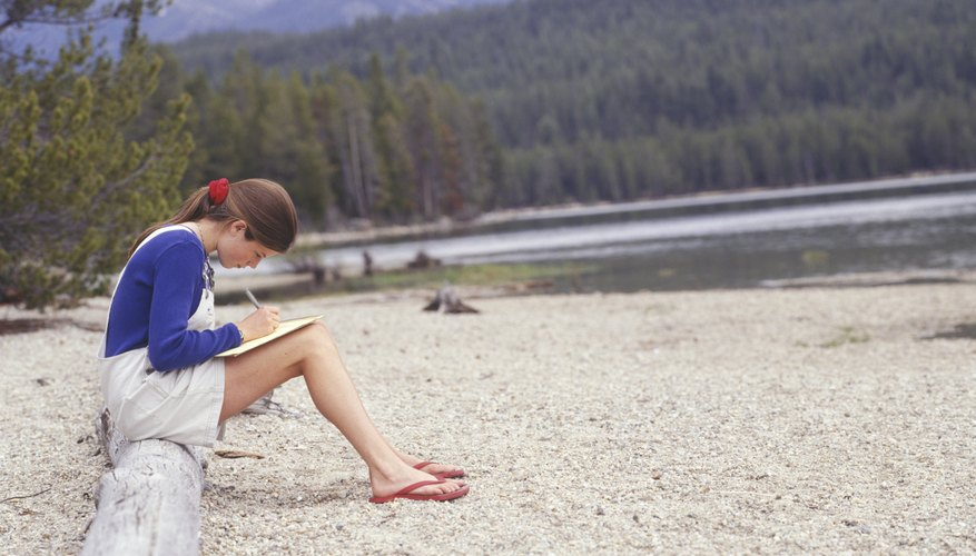 A teen sitting on a log and writing a letter by the lake in summertime.