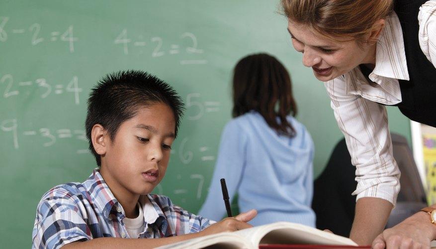 Teacher helping student at desk.