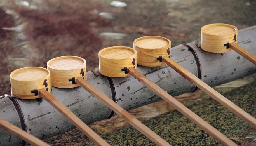 Shinto followers purify themselves with sacred water  before entering a shrine.
