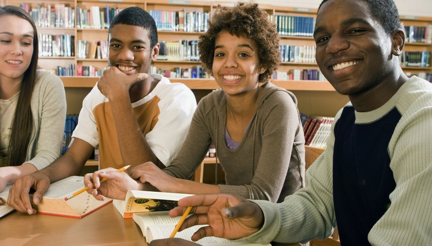 Smiling high school students in library.