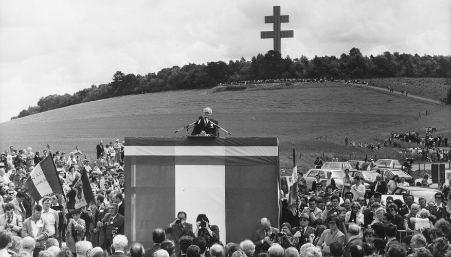 A Cross of Lorraine towering in the distance at a historic ceremony.