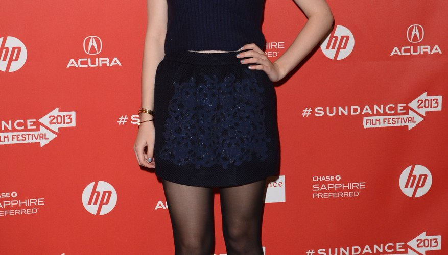 Dakota Fanning pairs an embellished navy skirt with sheer black tights for a sleek evening look.