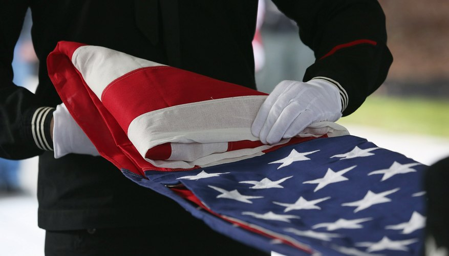 The flag code specifies that when a casket is closed, the flag must be draped across the casket so that the