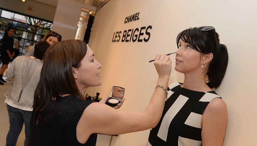 A make-up artist applying cosmetics in a department store.