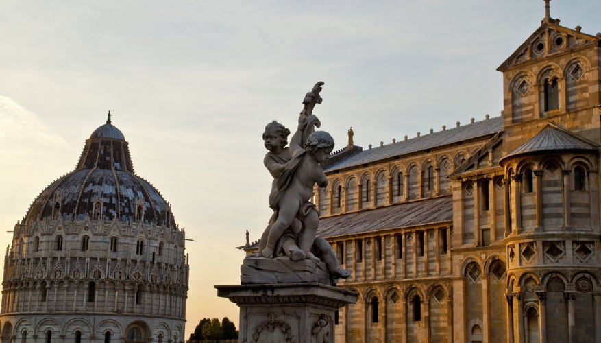 The top of the Leaning Tower of Pisa at sunset next to a statue and cathedral.
