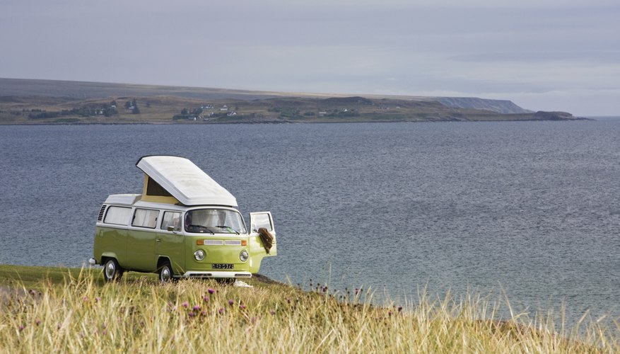 VW bus parked in a field overlooking water.